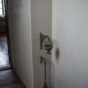 Naczynie z wodą święconą i kropidło w przejściu z zakrystii do wnętrza bazyliki.